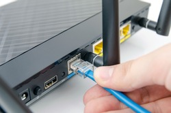 Man plugs internet cable into the router. router wifi ethernet connection network port wireless closeup concept