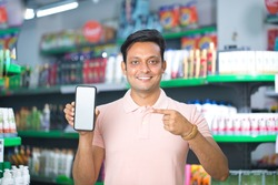 Man pointing at blank mobile phone screen in supermarket