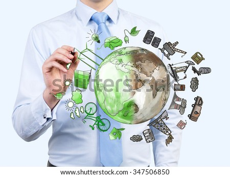 man pointing at the brown picture of oil industry components and green eco energy arranged in circle, earth in the centre, concept of environment #347506850