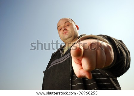 man pointing at you in front of blue sky