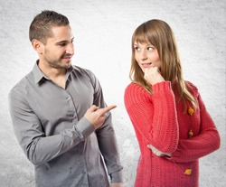 Man pointing his girlfriend over textured background