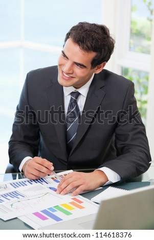 Man pointing out a graph while looking away in an office