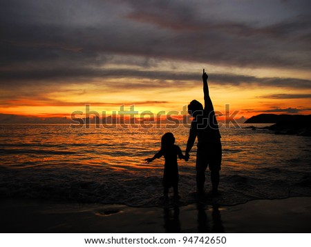 Man pointing to the sky showing something to kid during sunset