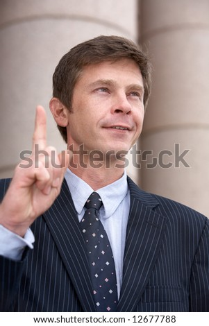 Man pointing up with index finger outside building