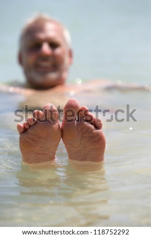 Man poking his feet out of the water
