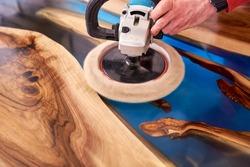 man polishing epoxy table close up.