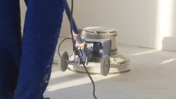 Man polishing marble floor in modern office building. Man works with grinding machine for floor