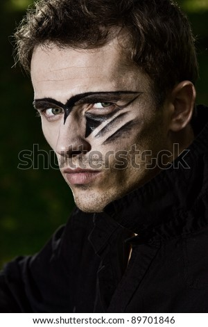 man portrait, hard handsome male model with military makeup - stock photo