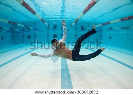 Man portrait wearing white shirt inside swimming pool. Underwater image.