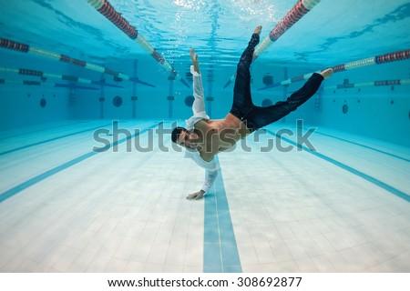 Man portrait wearing white shirt inside swimming pool upside down. Underwater image.