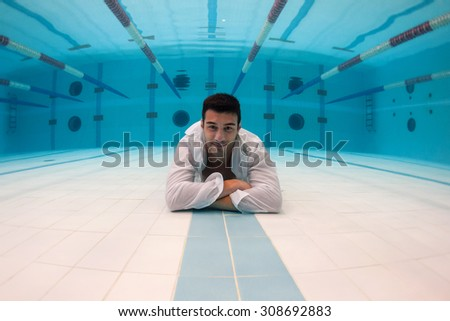 Man portrait with crossed arms wearing white shirt inside swimming pool. Underwater image.