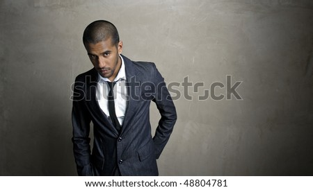 Man poses in his suit in front of grunge wall