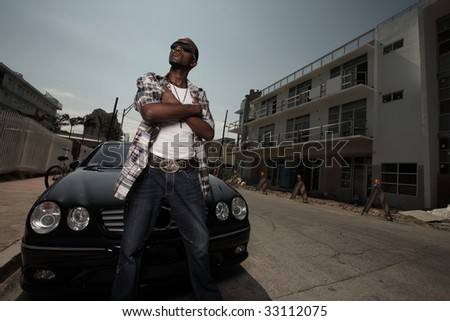 Man posing by a luxury car