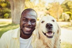 Man posing with a dog at park