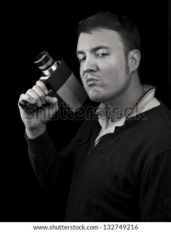 man posing with cine film / video camera as a gun. black and white portrait