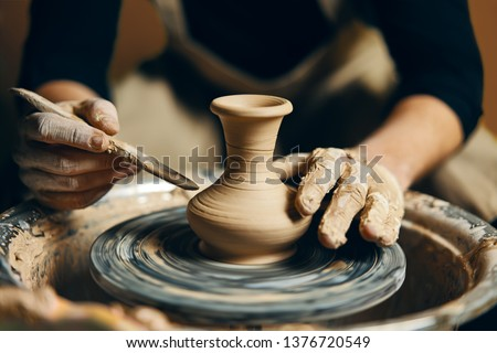 Man potter working on potters wheel making ceramic pot from clay in pottery workshop. art concept Сток-фото ©