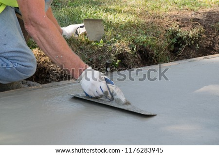 Man Pouring and Finishing a Concrete Driveway #1176283945