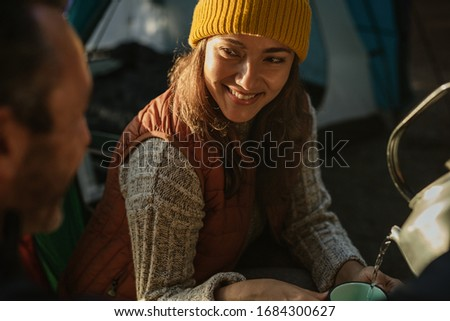 Man pouring coffee in woman's cup at campsite. Couple camping in nature having coffee. stock photo