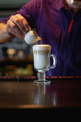 Man pouring frothed milk into espresso making latte coffee. Portrait orientation