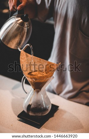 Man pouring water into a pour over coffee #1446663920