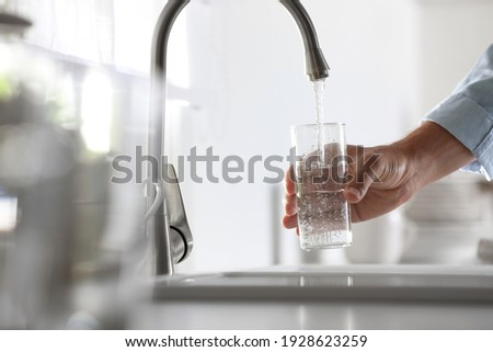 Man pouring water into glass in kitchen, closeup Foto stock ©