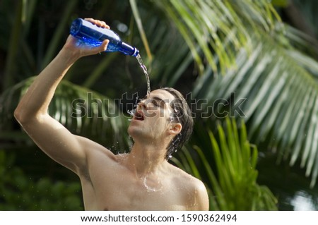 Man pouring water on face to cool off