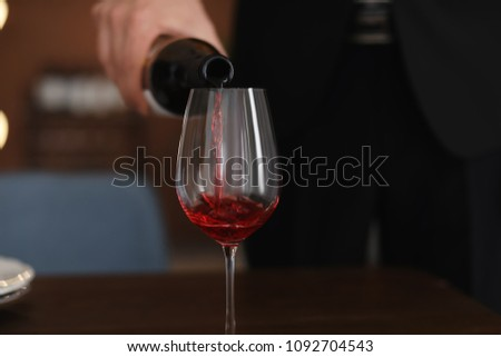 Man pouring wine into glass on table #1092704543