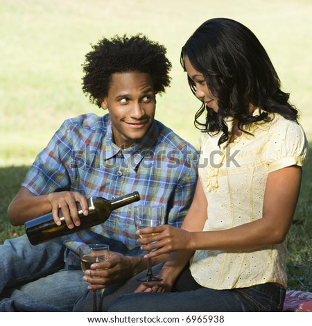 Man pouring woman glass of wine sitting on picnic blanket in park.