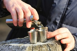 man pours alcohol from a flask into four steel glasses