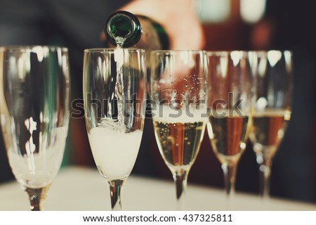 Man pours champagne in wineglasses #437325811