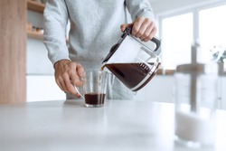 man pours himself a cup of coffee