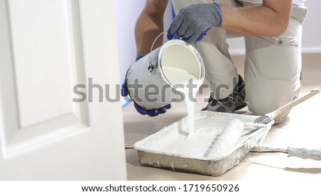 Man pours paint into the tray and dips roller. Professional interior construction worker pouring white color paint to tray. Foto stock ©