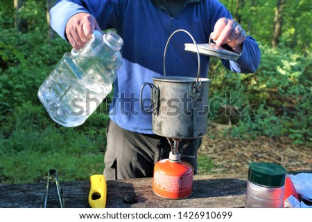 Man pours water into lightweight aluminum pot at campsite.  Making breakfast in camp on sunny morning boiling water from propane fuel canister requires natural resources like clean potable water. #1426910699