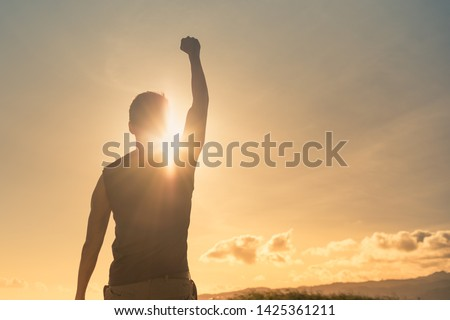 Man, power, victory, winning, hero concept. Strong young muscular male with fist in the air. ストックフォト ©