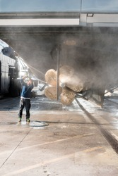 Man power washing the hull and propellers of a superyacht after haul out for shipyard period, with water spray causing a mist/haze in the air