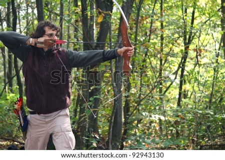 man practicing archery in a forest