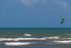 Man practicing kite surfing near  Forte Beach in Mata de São João in Bahia - Brazil. Strong wind, sea and sky with different shades of blue and the horizon line on a sunny day.