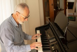 Man practicing playing the piano in the living room of his home after retirement from work.