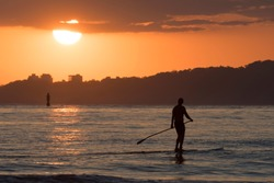 Man practicing stand up paddle in bahia de santos at sunset