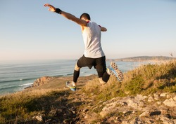 Man practicing trail running with a coastal landscape in the background