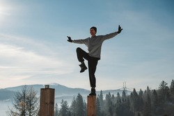 Man practicing yoga and balancing exercises in the winter mountains and enjoying life. Copy, empty space for text.