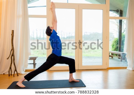 Man practicing yoga indoors in a retreat space doing Warrior 1 pose - Viradhadrasana I #788832328