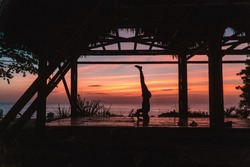 Man practising a headstand with sunset background. Yoga retreat with bamboo hut and red, orange sky. Handstand balance. Shot in Montanita beach, Ecuador.