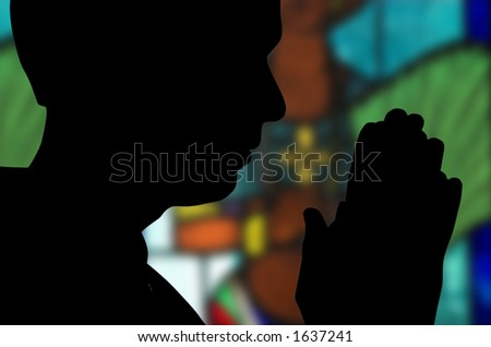 Man praying in front of stained glass window