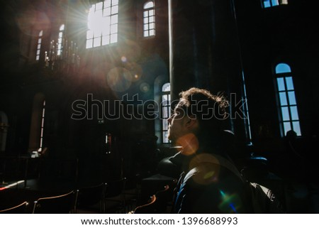 Man praying in the darkness when the light comes through the window. Revelation moment. Finding the purpose, finding myself. Russian orthodox church or chapel. #1396688993