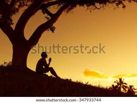 Man praying, meditating in harmony and peace at sunset