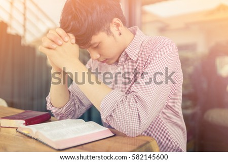 man praying on holy bible in the morning.teenager man hand with Bible praying,Hands folded in prayer on a Holy Bible in church concept for faith, spirituality and religion