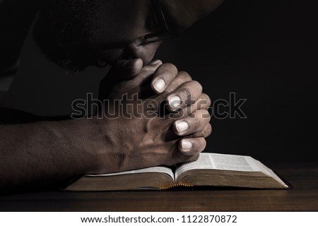 Man praying to God on a Bible in a dark place.  #1122870872