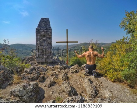 Man Praying to, Worshipping, Praising the God, on the Top of a Rocky Mountain with huge Cross. Strong Christian.
