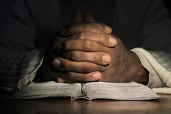 man praying with the bible on black background stock photo